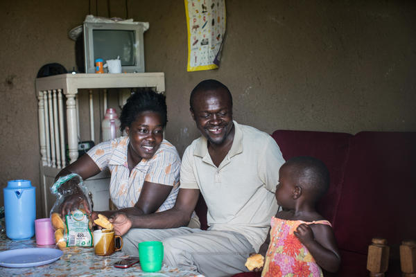 Otieno and his wife, Bentah, laugh as Gloria munches on some bread. Gloria used to cry all the time because she was hungry. Now Otieno can guarantee her solid food every day.