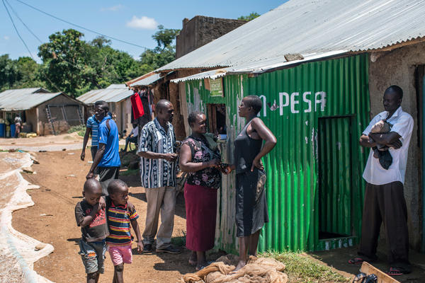 Otieno withdraws money from his M-PESA account, a widely used banking system linked to people's phones. GiveDirectly wires its monthly payouts to the villagers through M-PESA.
