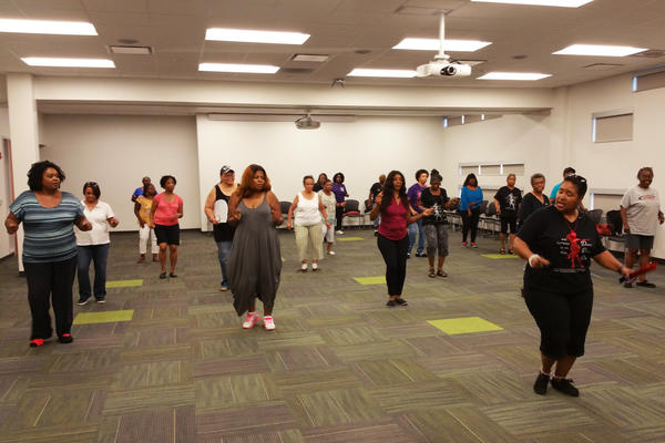 "Dawn, ""the Dancin' Deeva,"" helps a group of women learn new moves during an adult line dancing class.  The Harvey Library offers the free class weekly."