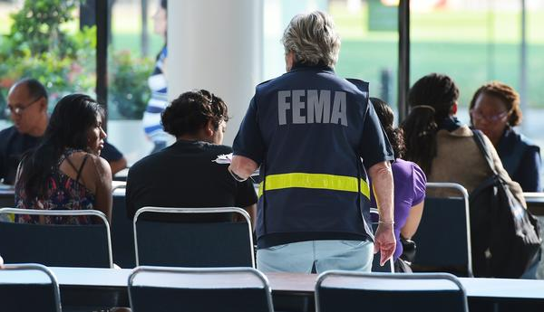 An official with the Federal Emergency Management Agency talks to people at Houston's George R. Brown Convention Center, which has been a shelter for evacuees from Hurricane Harvey, on Sept. 2.