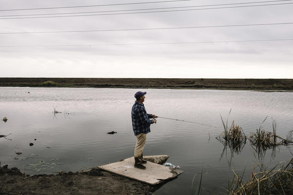 Buddy Melancon fishes on Falgout Canal Road in rural Terrebonne Parish, near the Gulf of Mexico.