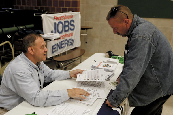 In this Nov. 2, 2017, photo, a recruiter in the shale gas industry, left, speaks with an attendee of a job fair in Cheswick, Pa.