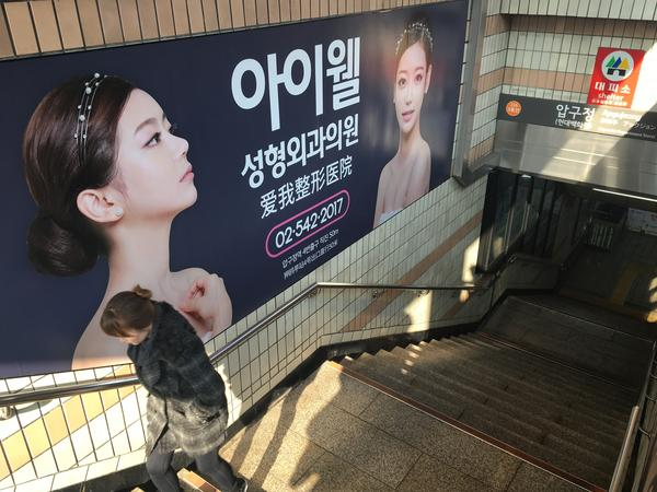 Ads for plastic surgery clinics line both sides of the stairwell going into a subway station in the Gangnam district of Seoul.