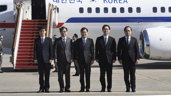 South Korea's national security director Chung Eui-yong, center, National Intelligence Service Chief Suh Hoon, second left, and others in the delegation pose before boarding an aircraft as they leave for Pyongyang at a military airport south of Seoul Monday.