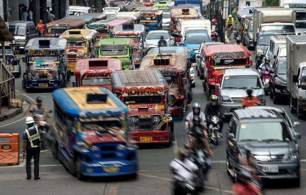"""Jeepneys, often known in the Philippines as """"King of the Road,"""" join traffic on a busy street in Manila last May. Authorities are moving to phase them out, citing pollution and safety concerns."""