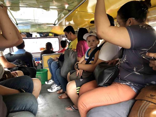 Passengers ride in a jeepney in Manila. Depending on the size, a jeepney can hold up to 20 people. While the vehicles have designated routes, they don't have designated stops, meaning riders hop on and hop off whenever they choose.