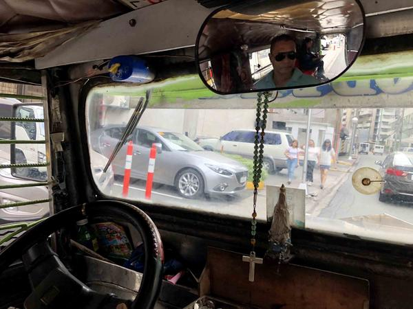 Raffy Solongon (in rear-view mirror), 47, drives his jeepney through Makati City in Manila. He earns about $10 a day and is one of thousands of drivers who say they can't afford the new jeepney model the government wants them to buy.