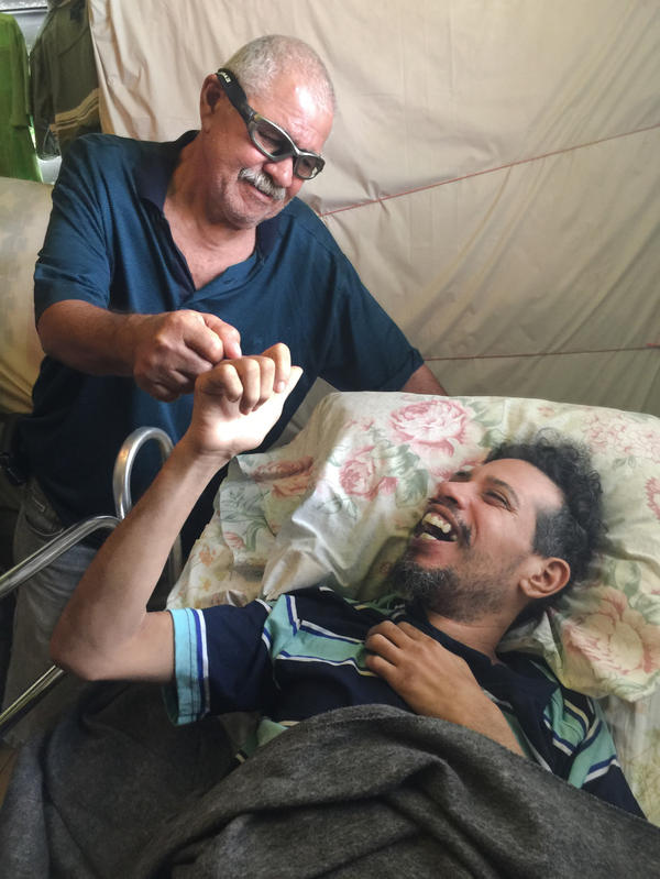 Osvaldo Martinez (left) takes care of his increasingly disabled son, Osvaldo Daniel Martinez, who is on Medicaid. With few neurologists on the island, they have not been able to get the younger Martinez an appointment with a specialist who could formally diagnose and treat him.