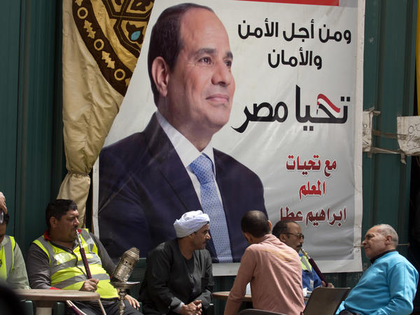 """People chat and smoke under an election campaign banner for Sisi, with Arabic that reads, """"for the sake of the nation security,"""" in Cairo on March 24."""