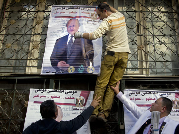 Supporters of Egyptian presidential candidate Moussa Mustafa Moussa hang his campaign posters near his headquarters in downtown in Cairo on March 21.