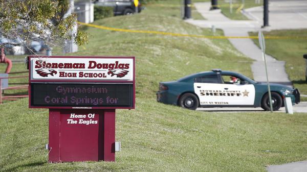 Law enforcement officers block off the entrance to Marjory Stoneman Douglas High School on Feb. 15 in Parkland, Fla. A day earlier a gunman opened fire in the school, killing 17 people.
