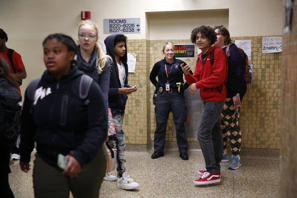 In between classes, the police officer assigned to the school, Pam Gronski, jokes with students.