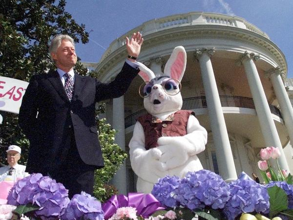 President Clinton, accompanied by the Easter Bunny, waves to White House visitors on the South Lawn during the White House Easter Egg Roll in 2000.