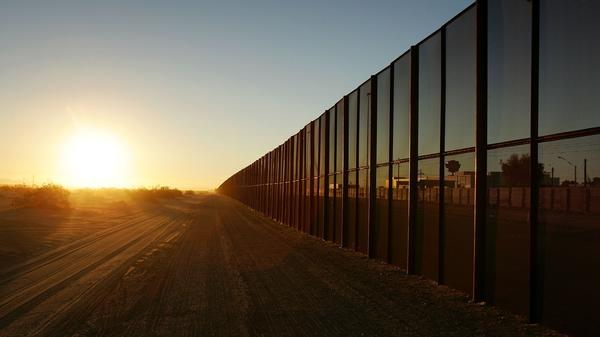 A metal fence runs along the U.S.-Mexico border east of San Luis, Ariz.