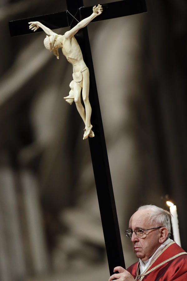 Pope Francis holds a crucifix as he celebrates the Good Friday Passion of Christ Mass inside St. Peter's Basilica, at the Vatican, on Friday.