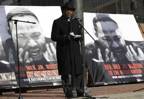 Nation of Islam Minister Rodney Muhammad reads a short passage from Martin Luther King Jr.'s last speech before King's assassination 50 years ago this week during a remembrance Monday on City Hall Plaza in Boston. (AP Photo/Steven Senne)