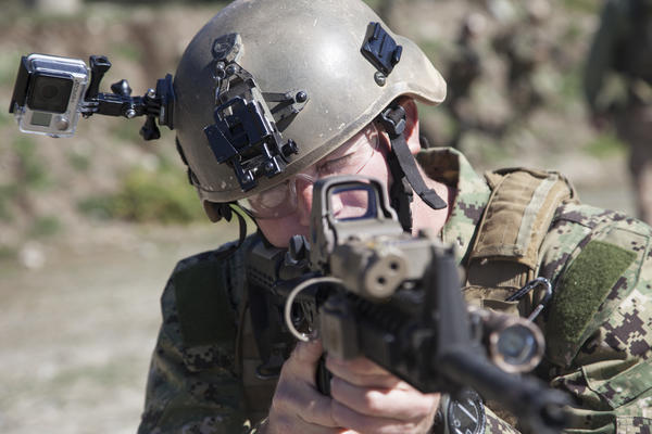 With a camera attached to his helmet, Navy Specialist 1st Class Benjamin Lewis participates in a training exercise. Combat Camera photographers are trained to shoot both cameras and weapons to photograph military operations.