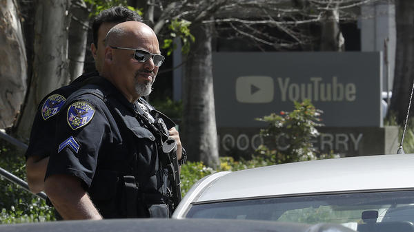 Police officers keep watch outside YouTube's headquarters Tuesday in San Bruno, Calif., after a woman opened fire on workers there. The shooter had vented her frustration with YouTube's recent decision on advertising revenue.