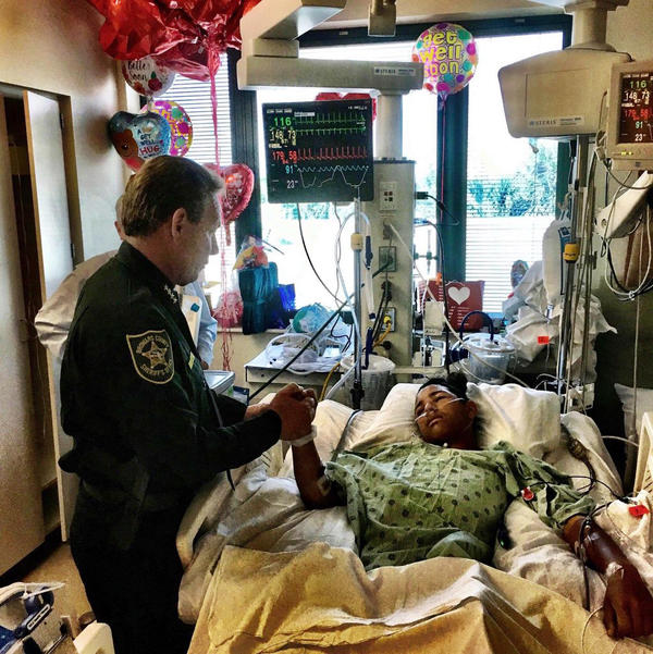 Sheriff Scott Israel, holds the hand of Anthony Borges, 15, a student at Marjory Stoneman Douglas High School in a photo released Feb. 18. Anthony was the last Parkland survivor to be released from the hospital and now his lawyer is preparing a lawsuit against the Sheriff's Office and others in connection with the shooting.