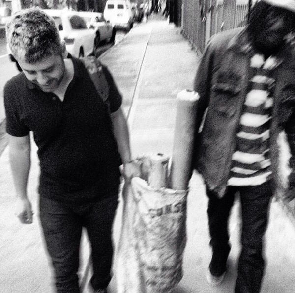 The author, left, with Nabay, carrying a set of Sierra Leonean bamboo bubu pipes in Brooklyn.