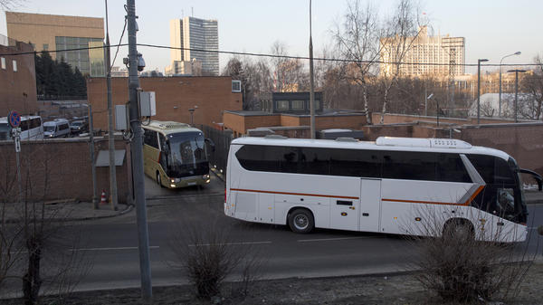 Buses believed to be carrying expelled diplomats leave the U.S. Embassy in Moscow on Thursday. The Kremlin ordered 60 American diplomats to leave Russia by Thursday, responding to a similar move by the U.S.
