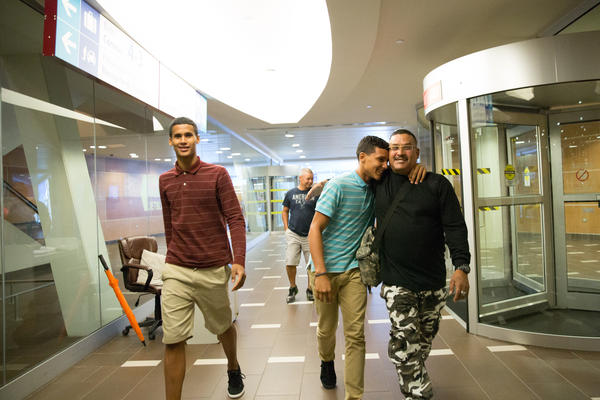 Guillermo Class reunites with his two sons in the San Juan Airport. He sold his car to fly them back to Hartford.