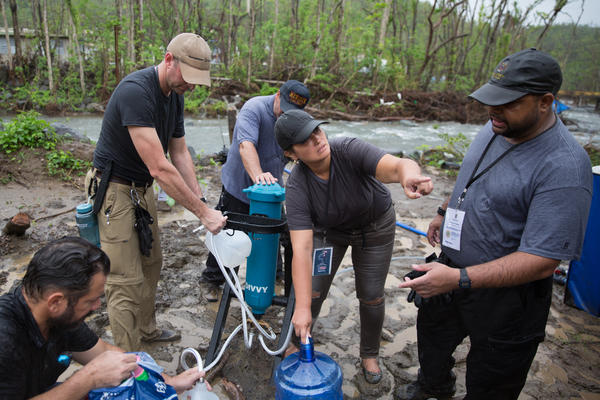 """A team of Connecticut veterans and volunteers -- self-described as the Puerto Rican """"water dogs"""" -- pumps water from a river in Salinas, Puerto Rico through a mobile filtration and purification system for residents there to drink."""