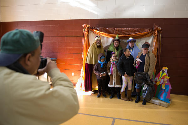 A family poses for a picture with the Three Kings, played by members of the Hartford community in a city recreation center.