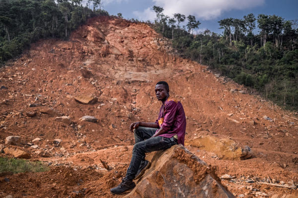 Samuel Senessie, 25, at the site of last year's mudslide. He lost five members of his family and his home. He says he has not received the government support to which he should be entitled.