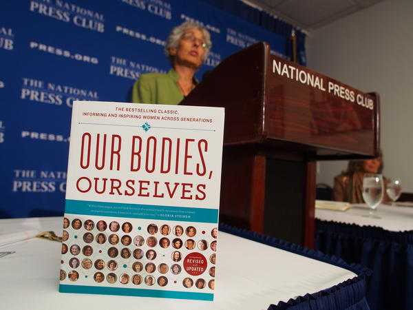 Judy Norsigian, executive director and founder of Our Bodies, Ourselves, speaks behind a copy of the women's health guide at the National Press Club in 2012.