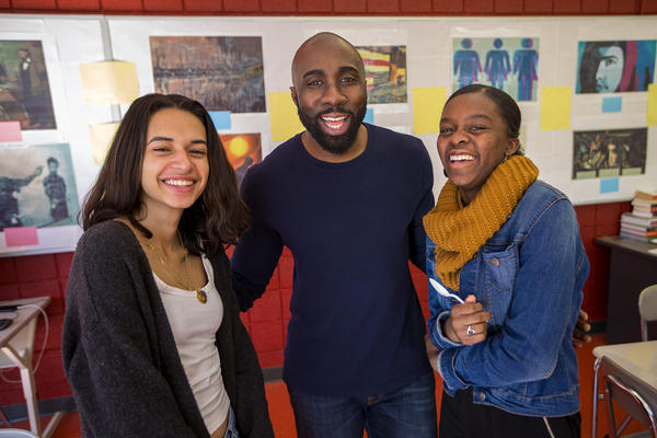 Cambridge Rindge and Latin School history teacher Kevin Dua, flanked by Victoria Angeles, left, and Lorra Marseille, members of the Black Student Union. (Jesse Costa/WBUR)