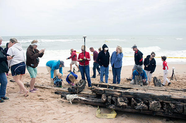 Lori Collins (center, in red) holds a scanning tool while crowds look at a shipwreck on Ponte Vedra Beach earlier this month.