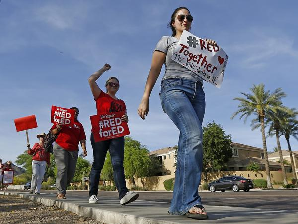 Arizona teachers marched in in front of a Phoenix radio station Tuesday, waiting for Republican Gov. Doug Ducey to show up for a live broadcast.