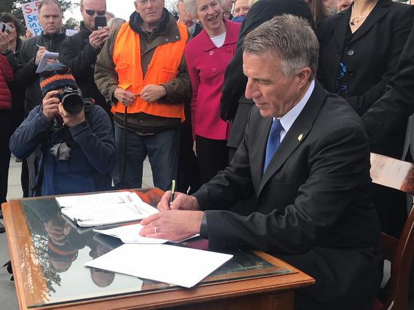 Gov. Phil Scott signs three pieces of gun control legislation amid boos and cheers on the front steps of the statehouse Wednesday, April 11, 2018.