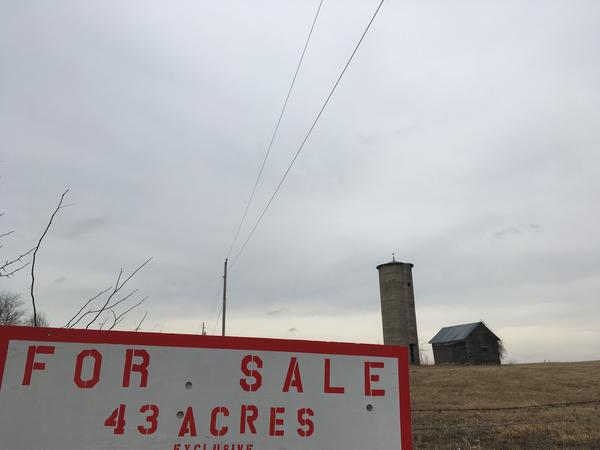 Farm buildings sit on land that's for sale in Clay County, Missouri. Nearly 40,000 people have moved to the county since 2000.