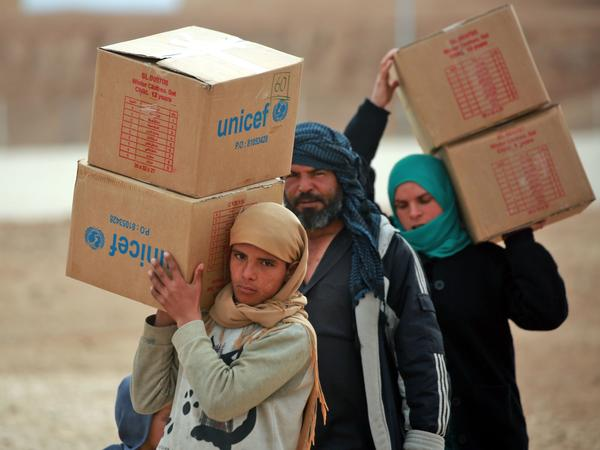 Displaced Syrians, who fled their homes in the city of Deir ez-Zor, carry boxes of United Nations aid at a camp in Syria's northeastern Hassakeh province in February.