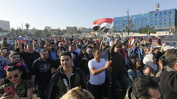 Syrians condemn the U.S.-led airstrikes, at a protest Saturday at the Omayyad Square in Damascus.