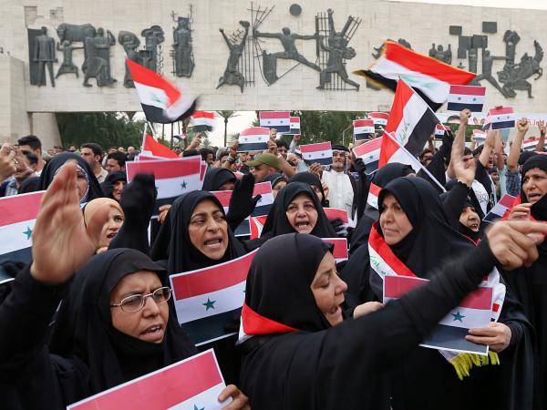 Protesters shout slogans as they wave Iraqi and Syrian flags during a protest against the U.S.-led missile attack on Syria, in Tahrir Square, Baghdad, Iraq, on Sunday.