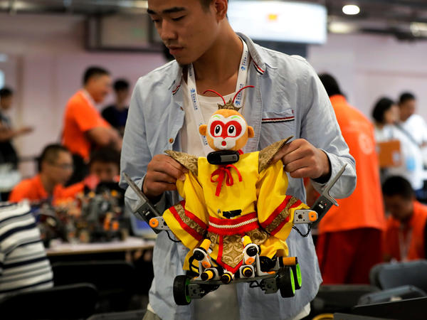A college student carries his robot depicting the Chinese mythical Monkey King for a competition at the World Robot Conference last August in Beijing.