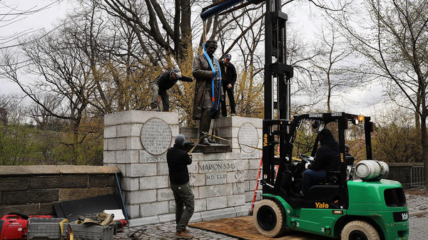A statue of surgeon J. Marion Sims is taken down from its pedestal in Central Park on Tuesday. A New York City panel decided to move the controversial statue after outcry, because many of Sims' medical breakthroughs came from experimenting on enslaved black women without anesthesia.