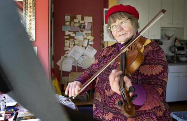 Betty Hauck, a musician suffering from hearing loss, plays her viola at home in Cambridge, Mass. (Robin Lubbock/WBUR)