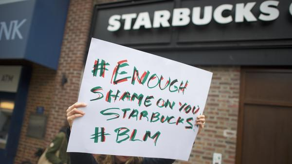 Protesters demonstrate outside a Starbucks in Philadelphia on Sunday, several days after police arrested two black men who were waiting inside the Center City coffee shop. The chain has announced it will close for an afternoon on May 29 for companywide racial-bias training.