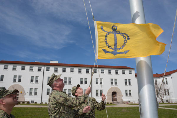 Sailors at Naval Air Station Pensacola, Fla. raise a flag to recognize the station's success at retaining personnel. The Navy recognizes units that do a good job keeping sailors in the service.