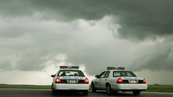 Police officers in Lawrence, Kan. watch thunderstorms move past the city in 2008.