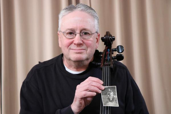 BPO Cellist Robbie Hausmann holding a picture of his German great grandmother Toni Marcus and his mother sitting on her lap.