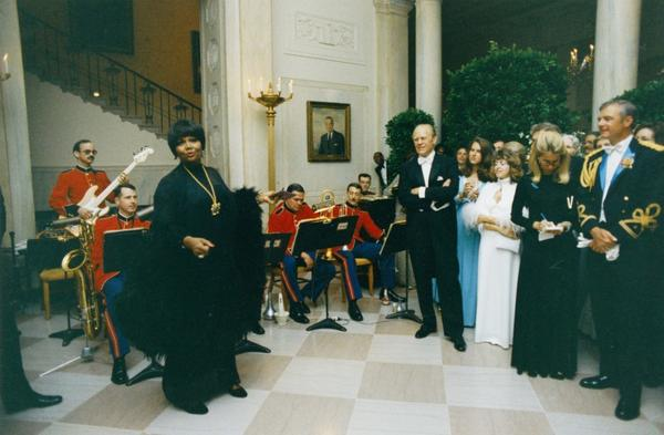 President Gerald R. Ford watches Pearl Bailey perform in the White House Entrance Hall during a State Dinner in May 1975.