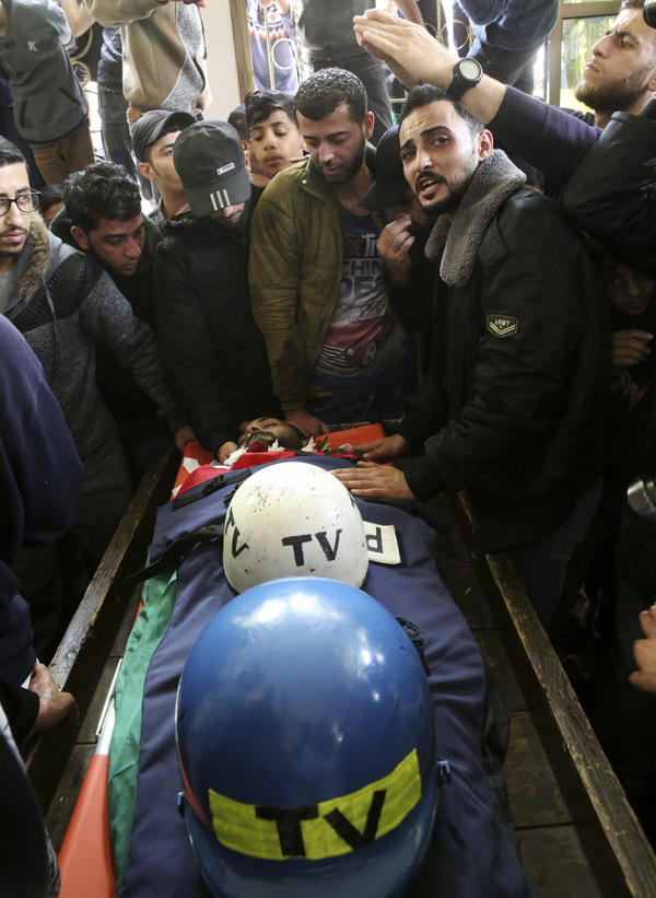 Mourners gather Thursday around the body of Palestinian journalist Ahmed Abu Hussein, who was killed by Israeli troops while covering a border protest. Resting with him are his helmets marking him a member of the television media.