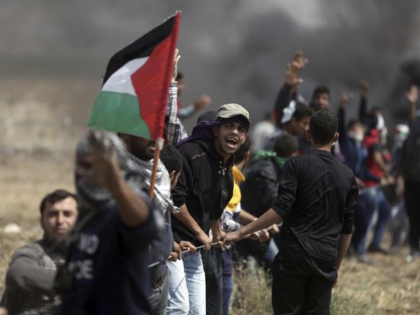 Palestinian protesters pull at part of a fence placed by the Israeli army during the demonstration Friday.