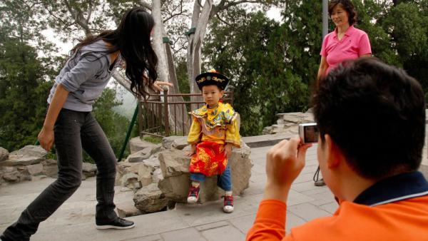 "A Chinese family coaxes their son to pose in a ""little emperor"" costume at a park in Beijing last year. China introduced its one-child policy for urban Chinese in 1976, resulting in a generation of sibling-less offspring."