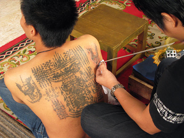 A disciple of Master Noo Ganpai tattoos elaborate Buddhist designs onto the back of a customer.